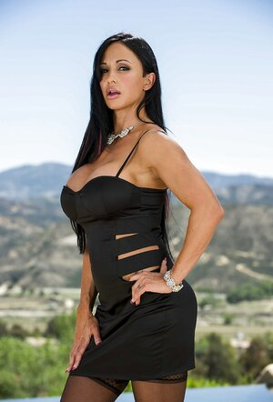 Hot adult entertainment photoshoot of Jewels Jade in black dress posing in vernal air by a pond
