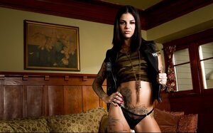 Exceptional inked model poses quite naked dressed only in leather jacket