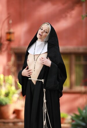 Skinny blonde nun provocatively shows small tits and plus cunny hidden under outfit