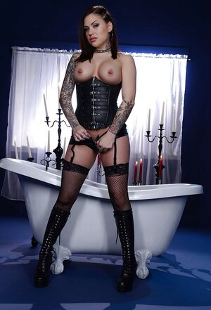 Impeccable slut in corset and fishnet stockings waits for fucker in bathroom