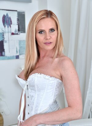 Lady in a white corset leaves it on while exposing her trimmed peach